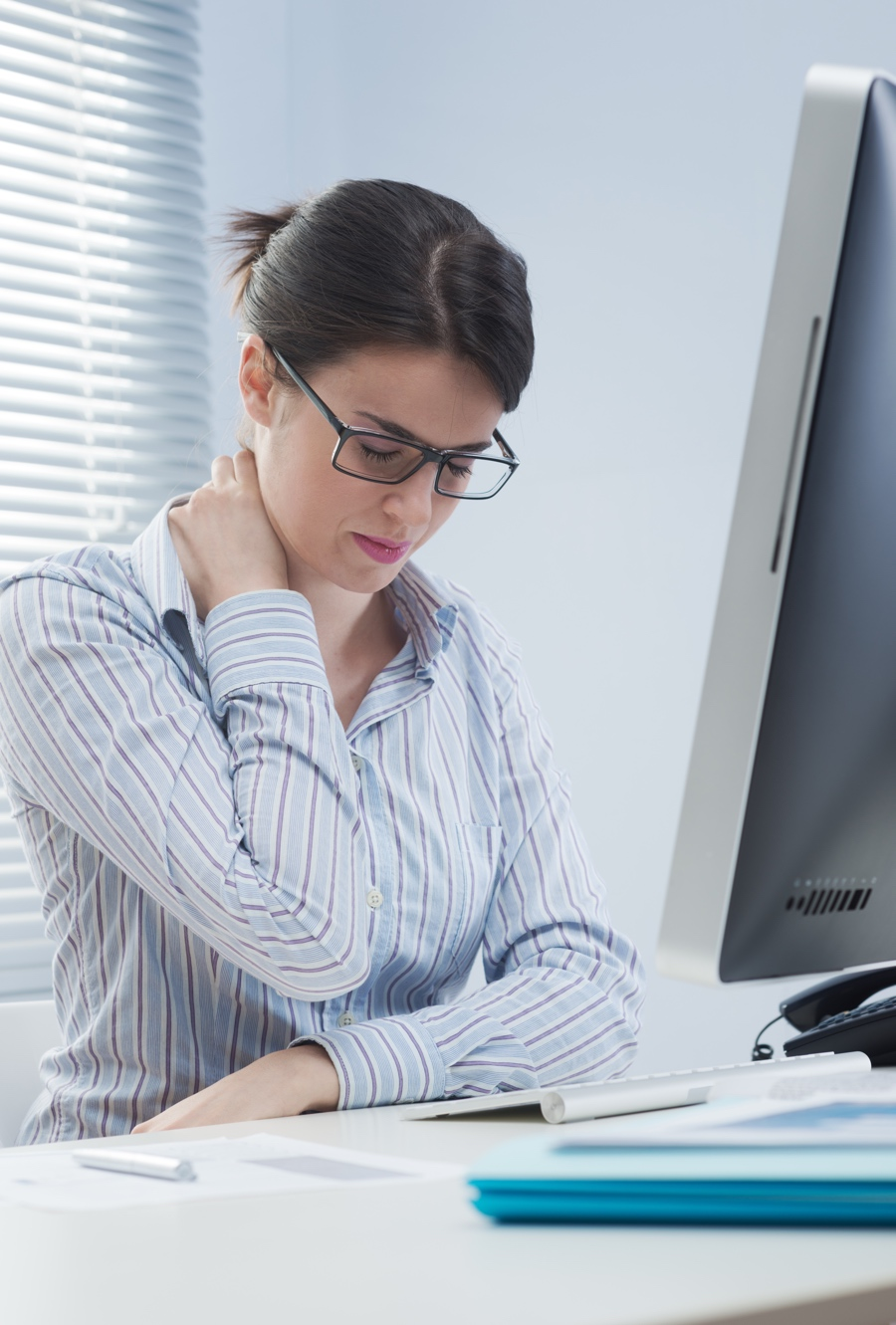 Female employee seated rubbing neck area