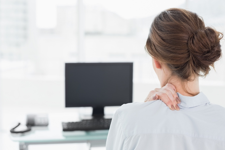 Female office worker clutching neck